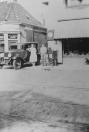 Anne de Jong was een der eersten in Gorredijk die radio's en andere electrische apparaten verkocht. Daarnaast verhuurde hij oopk auto's. zonder en met chauffeur. Op de foto staat zijn vrouw Jantje Kuipers tegen hun auto geleund. In het huis rechts is nu reisbureau Thomas Cook gevestigd (2005).