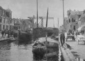 Een met turf geladen schip ligt in de sluis van Gorredijk om te worden geschut. Een langskomende bakker levert brood aan de schippersvrouw. (1931).