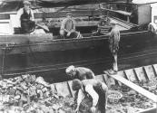 Hier word een schip geladen met turf, eerst het ruim vol en daarna nog een deklast. Het aantal korven á 50 stuks word geteld. De schipper (links) zit op de luiken.