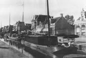 Deze tjalk ligt in Drachten aan één der kaden. Hij is geladen met turf die de schipper hier zal verkopen. Een handkar met turf staat al klaar om te worden afgeleverd. (Foto uit 1933)