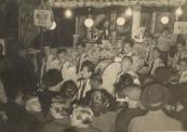 Het afscheid dat de familie Arjaans van het kermis bestaan nam te Gorredijk op 05-11-1955 ging niet onopgemerkt voorbij, het Gorredijkster muziekkorps Ad Altiore Concordia bracht s'avonds om 8 uur een serenade. Op de foto staat mevrouw Arjaans zichtbaar te genieten in haar Nougat & Suikerwerkenkraam. (Foto: Fam. Flikkema).