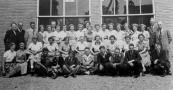 Ulo-klas met onderwijzers in 1952. Staande v.l.n.r.: de handwerkjuf, onderwijzer Jan v.d. Heide, gymonderwijzer R.Zaadstra, Jeltje de Boer, N.N., het hoofd Oege Bergmans, Joukje Kromhout, N.N., Akkie v.d. Sluis, Afke Meester, Geertje de Vries, Wieke de Boer, Tine de Hoop, N.N., Henny v.d. Duim, N.N., Nellie Veenland, Roelie Jelsma, Aaltje Brouwer, onderwijzer Gerhardus Feikema, onderwijzer Bertus Bootsma. 2e rij: Ietje de Haan, Annie Krikke, N.N., N.N., Lutske Koopmans, Janneke de Vroeg, Jannie van Dam, N.N., Jetske Hofstra, Willie Hoeksema. Vooraan: Harm Schroor, Johan Heida, Ybele Jonker, onderwijzer Antoon Bosveld, Jan Visser, Jochum Zwier, Dirk Dunant, onderwijzer Anne Oosterdijk.