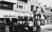 Hans de Boer (derde van links) brengt met paarsd en wagen draaibanken en ander materiaal naar de nieuwe ambachtsschool aan de Jodocus Heringastrjitte. De lessen waren eerst in de Marechausseekazerne en in de metaalwarenfabriek van Johannes Ymkes de Jong aan de Stationsweg gegeven.