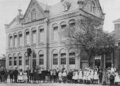 Foto van omstreeks 1900 waarbij de leerlingen van de in 1887 gebouwde Openbare Lagere school voor de fotograaf poseerden. Het pand rechts (afgebroken) werd in 1877 door 't Nut als kleuterschool gebouwd.