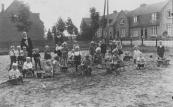 Deze grote zandspeelplaats lag voor de Nuts-kleuterschool . Naast juf. Looijenga zijn slechts enkele spelende kinderen herkend. Tinie Nauta, Piet de Jong, Geeske en Oene de Boer en Jan Visser. Op de achtergrond de eerste gemeentewoningen die kort na de eerste wereldoorlog werden gebouwd en in 2004 zijn afgebroken.