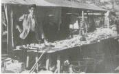 Koopman Klaas Idzinga op een markt, geflankeerd door een andere 'Klidzeman': Sierd Otten. Te koop: hamers, scheerkwasten, fluitketels en wat niet al.