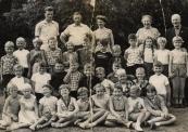 Openbare Lagereschool Kortezwaag 1957-1958. Achterste rij v.l.n.r.: Appie Postma, N.N., Hiltje Looyenga, Juf de Groot-Reinbergen., Chauffeur. 2e rij: Marinus de Vries, Sientje Pultrum, Elly Dijkstra, Luc Koopmans, Siepie de Vos, Otto de Vries, Teye v.d. Bij, Jan Seinstra, Wim van Dijk, Renske de Jong, Grietje Rozenberg, Arendje Bergsma. 3e rij: Anna Wil van Dijk, Harke Post, Jan Stoelwinder, Hannes de Vries, Rennie Hofstra, Hans v.d. Bosch, Eise Heida, Robbie Broers, Gerrit Kromsigt, Rink Post. 3e rij: Janna Rinsma, Lutske Dijkstra, N.N., Aaltje Veenstra, Alie Kromsigt, Loesje Blauw, Liesje Stoelwinder, Annie Jongsma, Annie Boomsma.