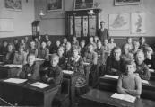 O.L.school 1931-1932. 1e rij banken rechts: Harm Jan Bijlsma, Wiebe de Boer, Ernst Huisman, Aaltje v/d Heide, Hennie de Vos, Wimmie Teijema, Sjoerd Nauta, Piet Mast. 2e rij: Wouter Oosterhout, Klaas v/d Wal, Wobbiena Drenth, Bettie Otter, Jentsje Nauta, Geert v/d Akker, Doetie Westra, Dineke Wagenaar, Gerrit Krist, Jan Zuiderbaan, Jantje Meijer, Stien de Jong. 3e rij: Rienie Riedstra, Geertje Crom, Koos Mensinga (Loopstra), Auke Klazema, Jan Sijtsema, Jaap Schilstra, Anneke v/d Sluis, Sabina Jonkers. 4e rij: Heine Drenth, Wiepie Keuning, Willy v/d Pol, Pietje Nutters, Jantje de Groot, Jitske v/d Werf, Boukje v/d Wijk. Onderwijzer Jouke de Vos.