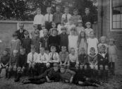 O.L.school op het schoolplein 1922. V.l.n.r. achter: Broer Lamerus, Jan van Dam, Henny Boelens, Hans Dijkstra, Abel Blauw, N.N., 2e rij: Mr. Visser, Minne Bijlsma, Mieny Ebbinge, Trijntje Bijlsma, Rienie Geveke, Akke Biesma, Marie Bouwer, N.N. 3e rij: Christine v/d Akker, Martha Bijlsma, Zus Beenen, Annie Faber, Adriaantje de Boer, Doetje Dijkstra, Mieke Ebbinge, Aaltje de Groot, Renske Drenth, Trijntje Bijlsma, Romkje de Boer. Voor: N.N., Jacob Bijlsma, Wiebren de Boer, Bonne Beun, Willem Drenth, Teun Glas, Albertus Drenth, Broer de Boer, Heine Drenth, Hendrik Beenen, Wilhelm Beenen. Op de grond: Folkert Coehoorn, N.N.