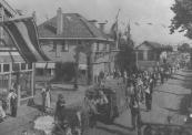 Optocht op 5 mei 1945, hier op de Stationsweg/ Hoofdstraat. Links de rietwinkel van Louw Kniezenburg.