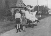 Optocht op 5 mei 1945. Hier op de Nijewei voor het huis van fotograaf H.C. v/d Meer.  Voor de versierde wagen staan Jan en Hilda Tabak. Op de wagen Billy (Sybilla) v/d Meer, een dochter van de fotograaf.