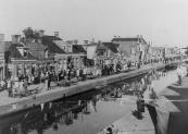 Optocht op 5 mei 1945, hier aan de Molenwal. Op de vaartkant liggen de resten van de bovenbouw van de hoofdbrug die de Duitsers in april hadden laten opblazen.
