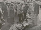 1992 Oktober, Lang niet alle plekken in de Hoofdstraat van Gorredijk waren gisteren bezet. De klompenverkoper leek nog wel aardig zaken te doen, maar de aanvoer van vee op de Gerdykster Merke was weer minder dan vorig jaar. Ruim dertig stuks - zeventien koeien, drie paarden en twaalf schapen - zijn gisteren aangeboden. Jan de Vries uit Hoornsterzwaag, met veertien stuks vee de grootste aanbieder, denkt dat de Merke een aflopende zaak is. It wurdt alle jierren minder. Dat hat ek te krijen mei de feemerke yn Zwolle dy't tagelyk halden wurdt. Mar ik bin myn bisten wol kwytrekke. Marktmeester Tjeerd Popkema ziet het minder duister in. It minne waar moarns hat üs parten spile.( Foto LC Jan de Vries)