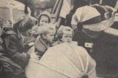 1960 Oktober, Het was nog rustig in de vermaakssektor, voorzover men daarbij bloot stond aan de regen. En daarvan hebben de kleintjes geprofiteerd, er was plaats en aandacht voor hen. Hier zweven vier meisjes in een vliegmachine, aan de gezichten van de kleinsten is te zien, hoe snel en hoe móói het ging.