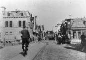 April 1945. Een lid van de Binnenlandse strijdkrachten met armband fietst richting hoofdbrug. Het Postkantoor links was zwaar beschadigd door het vuurgevecht met de Duitsers die de brug gingen opblazen. Er werd een grannat door een der dakkapellen geschoten. Tijdens het gevecht kwam Gerk Numan om het leven.
