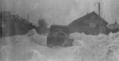 Foto út: 'n plaatsje mei 'n praatsje, Hans de Jong, Woudklank 28 april 2002.  Dit stie derby:   Hoog opgejaagde sneeuw op 16/17 januari 1940 nabij het tramstation. Geen enkele tram rijdt meer; ook de auto is ingesneeuwd. De sneeuw werd vanaf de weilanden noordoostelijk van de Stationsweg door stormachtige winden aangeblazen. Dat gebeurde via de toen nog openliggende ruimte, die in de volksmond 'Siberië'werd genoemd. Nu bevindt zich daar het appartementencomplex 'It Station'. (Foto: Anne van der Muur). Hantje Jan Bottema, Gorredijk, gemeente Opsterland. Afgegeven: 7-4-1928