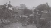 Een dame en heer poseren op bijzondere wijze op de Nijewei tijdens de ringrijderij. Op de achtergrond de openbare lagere school van Gorredijk (nu Museum Opsterlan) en rechts ervan waarschijnlijk de circustent van Teutenberg. Een foto uit één van de jaren 20 in de vorige eeuw.