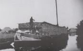 De met turf hoog opgetaste schuit van schipper Beyert van Drachten nadert van het zuidoosten uit de Boppedraai. De turf is afkomstig uit Drenthe. De foto werd in 1945 gemaakt.