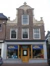 Pand met zadeldak tegen halsgevel met rijk gebeeldhouwde klauwstukken en bekroning in de Friese Lodewijk XIV-stijl. Lambrequins onder de klauwstukken en het topvenster. In de top twee sierankers; op de verdieping en in de top Zesruitsvensters.