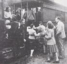 Albert Jans (rechts) haast zich op 18 augustus 1945 in de tram te stappen. Enkele ruiten van het rijtuig zijn nog vervangen door hout. Rechts: Corry Beenen.