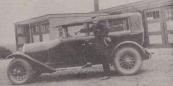 Kameleon-schrijver Hotze de Roos met de eerste 'bedrijfsauto' van zijn vader, aannemer Ruurd de Roos. De auto was bestemd voor langere tochten buiten de provincie. Op de achtergrond de autoboxen van garage Hendrikus de Boer in Gorredijk. (foto: Jan Dam)