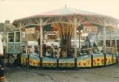 Hobbelende Geit 1987   Een foto uit het jaar 1987 gemaakt tijdens de najaarskermis van Gorredijk met zicht op de Golfbaan ook wel de hobbelende geit genoemd. Dit exemplaar betreft een originele nostalgische kermisattractie uit het jaar 1920 welke jaren lang in expoitatie was van de bekende familie Arjaans (Dirk) uit Joure. Op de attractie bevinden zich verschillende uit hout gesneden attributen welke voornamelijk best...aan uit dieren. In de middag draaide de attractie als kinderzaak en maakten dezen rustig de golvende beweging waarna om 20:00 uur s'avonds de versnelling een aantal tandjes hoger werd gezet en het voor de jeugd vooral goed vasthouden was. Voor wie er niet genoeg van kreeg was het de kunst om de pluim te vangen wat resulteerde in een gratis rit. Deze editie van de Gordykster najaarskermis is vermoedelijk de laatste kermis voor Arjaans geweest met de Golfbaan waarna deze is doorverkocht naar de huidige exploitant Jent Boersma uit Anjum. Dirk en Ank Arjaans zijn nog altijd woonachtig in Joure en exploiteren hedendaags een Glazendoolhof op kermissen in Nederland, Duitsland en België. (Foto: KCM)