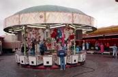Een foto welke gemaakt is tijdens de Najaarskermis van Gorredijk in het jaar 1986 met afgebeeld één van de bekendste spelen van de kermis, namelijk de grijpkranen in dit geval de Holly Cranes van de bekende Nico & Angenes Sipkema & zonen Cornelis (Corry) & Hendrik (Henny). Nostalgie want hier begon het allemaal mee, veelal ronde tenten waar de nodige man uren in gingen zitten. De Holly Cranes van Sipkema had een diameter van 8 meter en bood plaats aan 20 speelkasten, de tent ...werd helemaal van de grond af opgebouwd en uitgepakt in zo'n 8 uren tijd. Grijpautomaten gaan binnen de familie Sipkema reeds generatie op generatie, Cornelis Sipkema senior liet de tent nieuw bouwen in het jaar 1966 en deed hem op zijn beurt in de loop der jaren over aan zoon Nico. Het was echter de tijd dat de inklapbare containers hun intrede namen op de kermis, ook binnen de familie Sipkema, welke veel minder arbeidsintensief waren wat betreft de opbouw en de afbouw. De tent werd in 1991/1992 doorverkocht aan de neef van Nico, Berend Sipkema welke er enkele jaren mee rees. In 1995 kocht de oudste zoon van Nico & Angenes, Corry Sipkema de tent terug en heeft er nog een melkbussenspel in geëxploiteerd. Op de foto runt de neef van Nico (Berend Sipkema) samen met de toen 16 jarige Henny Sipkema (Jongste zoon van Nico & Angenes) de zaak. Henny exploiteert hedendaags nog steeds grijpkranen op de kermis. De tent is na Corry verkocht aan Nicolaas Sipkema (zoon van Berend Sipkema) welke er een kikkerspel in exploiteert op kermissen in Duitsland. Naast de Holly Cranes is de bekende Autoscooter van de familie Sipkema te zien. (foto: SKC)