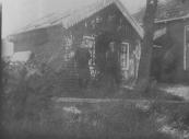 De ''stookhutte'' bij de boerderij van Auke Jongsma aan de Leijen (afgebroken). Links staat Pietje de Leeuw en rechts Anna Jongsma.