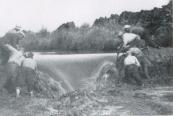 Een nieuw vak is klaar, de dam wordt doorgestoken (op blote voeten, om vastzuigen in de modder te voorkomen)