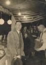 Op donderdag 3 November 1955 namen Johannes (Hannes) & Tjitske Arjaans afscheid van het reizende bestaan tijdens de najaarskermis te Gorredijk. De familie Arjaans was een bekende verschijning, zij hadden namelijk met hun Nougat & Suikerwerken kraam 34 jaar lang 2 maal per jaar een standplaats op de Gordykster kermis. Het afscheid ging niet onopgemerkt voorbij. Zo kreeg de familie uit handen van ma...rktmeester dhr. Ringenoldes een ets van de Leeuwarder waag en werden er muzikale klanken ten gehore gebracht door het Gordykster muziekkorps Ad Altiore Concordia. S'avonds na afloop van de kermis werd door de gezamelijk aanwezige kermisexploitanten afscheid van de familie Arjaans genomen in zalen Veensma, hier werden vele goede woorden en wensen uitgesproken. Op de foto hield Freerk Wiebe Flikkema (roepnaam Frits) een toespraak als secretaris van de Bovak Nationale Bond van Kermisbedrijfhouders van de afdeling Groningen - Friesland en Drenthe. (foto: fam Flikkema)