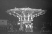 De fraaie opgooi Zweefmolen van de vooral in Friesland bekende Rapke Tuinstra uit Drachten. Rapke stond diverse keren op de kermis van Gorredijk, tijdens welke editie deze foto genomen is is niet precies duidenlijk maar het zal zo omstreeks 1958 geweest zijn. Rechts van de attractie is de in/uitgang van de Nieuwstraat te zien. (foto: SKC)