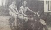 Zomers gekleed op de Harley Davidson van de P.E.B.er De Bruin. Deze was ingeschakeld bij het tot stand brengen van het transformatorgebouwtje vlakbij de viersprong in Kortezwaag omstreeks 1935/1936. De Buin was ingekwartierd bij smid Johannes Koelma. Op de motor diens dochters Nel (links) en Anneke. Op de achtergrond links Het Witte Huis (nog met balkon) , geheel rechts de eveneens wit-begevelde woning van Gosse de Boer , nu Hilbrand Rudolphy. (foto: Hans de Jong).