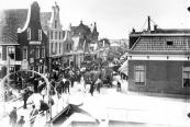 Te oordelen naar de wagens midden op de Zuid- West Dubbelestraat werd er een Woensdagse schapen en varkensmarkt gehouden. De foto werd omstreeks 1900 gemaakt, de brug heeft nog de lage boog met het Gemeentewapen. Die werd op verzoek van de N.T.M. (Nederlandse Tramweg Maatschappij) verhoogd., waarbij het wapen verloren ging.