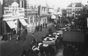 De Noord- Oost Dubbelestraat (Nu Hoofdstraat) tijdens de najaarsmarkt in oktober 1935, met Schansburg op de achtergrond. Rechts vooraan het reclamebord van bakker Gerrit Bruinsma die hier in 1934 was gekomen na het fallissement van bakker Sikke Hoekstra. In datzelfde jaar 1934 had Jelle Durks Sijtema het huis met winkel links van Obe Geerts Tasma gekocht.