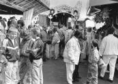 Deze afgebeelde foto is gemaakt tijdens de najaarskermis op zondag 25-10-1987, de mensen zijn in grote getale aanwezig op het marktterrein en vermaken zich uitbundig aan o.a. de op de foto zichtbare Autoscooter van de familie Buwalda en de Cake Walk met orgel van de familie Klinkhamer.