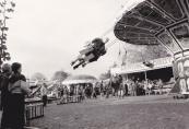 Een foto uit het jaar 1983 waarop de attracties Zweefmolen van Steenhuis , Vliegtuigmolen van de familie van der  Molen/Arjaans , Holly Cranes van de familie Sipkema/Speelman , Bootjesmolen Speedway Caroussel  van de familie Rampen en de Rupsbaan  Aerobic-Robot  van de familie Regter te zien zijn welke het volk amuseren op het Marktterrein.