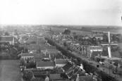 Een onbekend gebleven fotograaf beklom in 1917 de nieuw gebouwde schoorsteen van de olieslagerij aan de Kerkewal, van waaraf hij deze foto maakte. Rechts de Jaap Sikkes korenmolen aan de Molenwal.