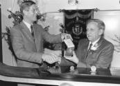 Harm Blokzijl (rechts) ontving op 15 december 1989 een erepenning uit handen van Burgermeester Van Bodegom wegens zijn diensten bewezen aan de ijsclub Hald Moed en eerder voor de hiermede gefuseerde ijsclub Eendracht