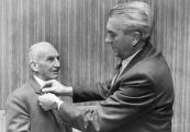 In 1987 wasDaniël Hendriks Kussendrager 40 jaar lid van de Friese Bond van Vogelwachten. Hier speldt zijn neef, Hendrik Klazes Kussendrager hem een ereteken op de rever.