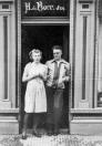 Romkje en Jelle in de deur van de bakkerswinkel in de Hoofdstraat, waar zijn ouders woonden